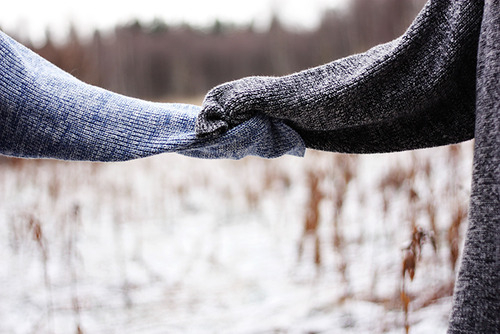 Two hands holding supporting each other during bulimia recovery.